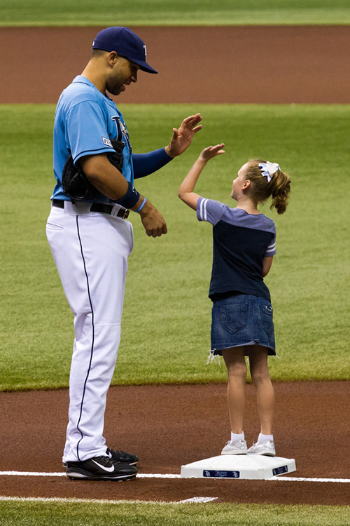 First baseman James Loney high fives a fan before the start of the game.