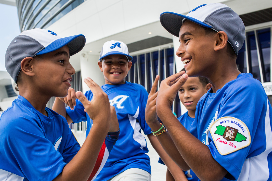 Members of the Aces 10U baseball team from Puerto Rico play hand games before the Marlins game.