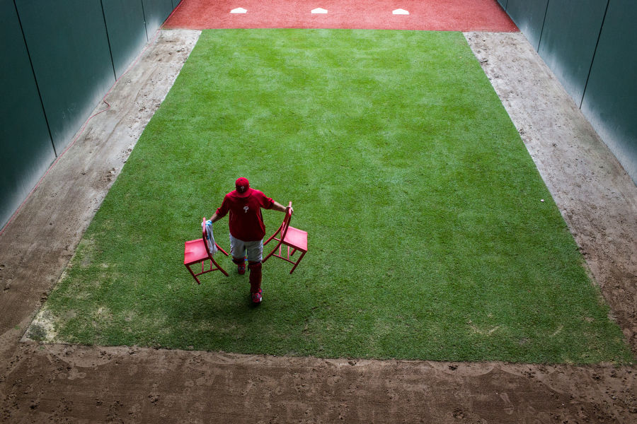 A Phillies bullpen catcher moves chairs out of the rain.