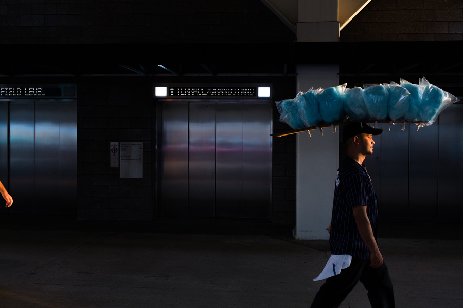 A cotton candy vendor walks through the upper concourse while balancing the candy on his head with no hands.