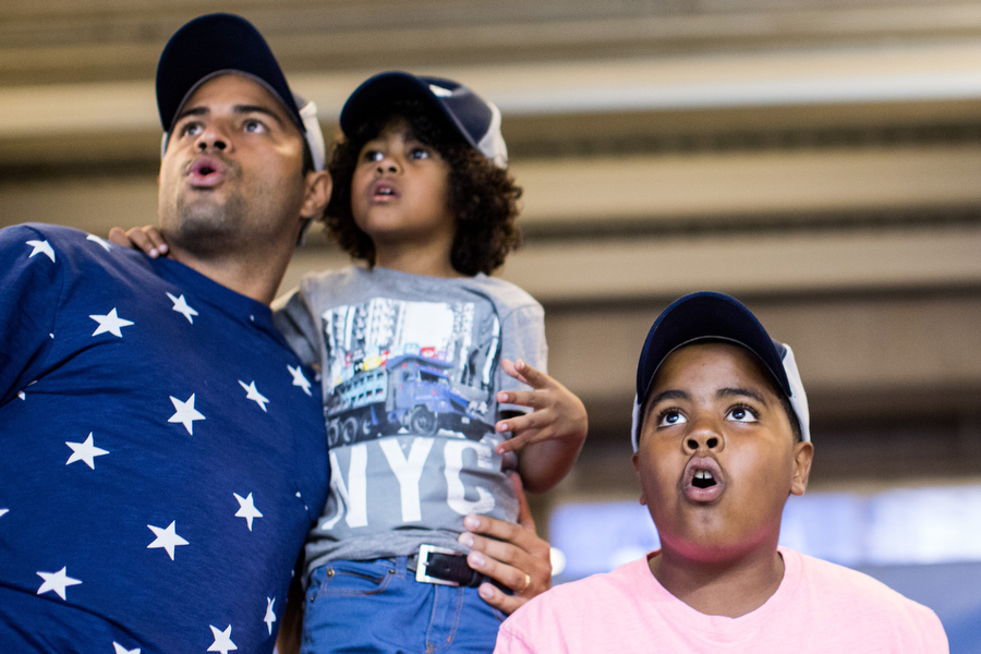 From left, Diego, his son Diego Andres and nephew Albert watch the trajectory of a Rangers player's home run. Diego and Diego Andres live in the Dominican Republic and had never before attended an MLB game.