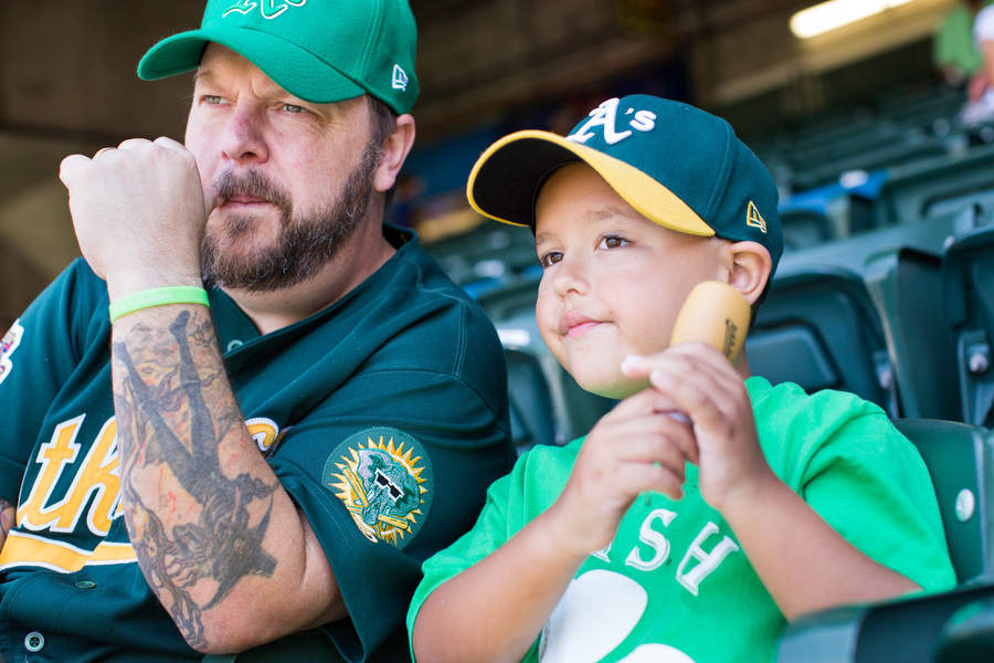 Lance Malone and his 7-year-old son Patrick, a catcher in little league, watch the game.