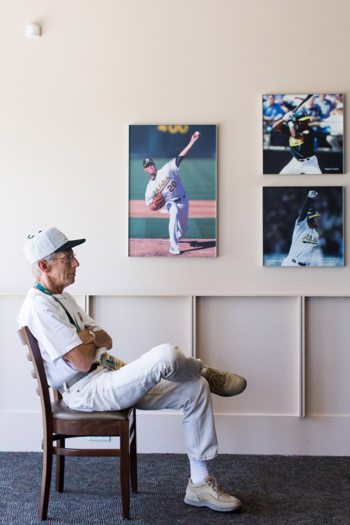 Jim, a season ticket holder, rests and watches the game on a television inside a large enclosed area on the plaza level behind home plate. Pictures of former A's greats hang on the walls.
