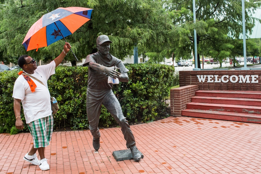 Robert Brandon shields a statue of former Astros second baseman Craig Biggio from the rain with his umbrella.