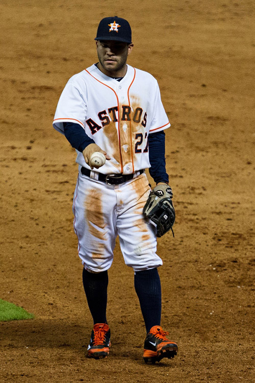 Astros second baseman Jose Altuve holds a ball with a split finger grip as he walks off the field.