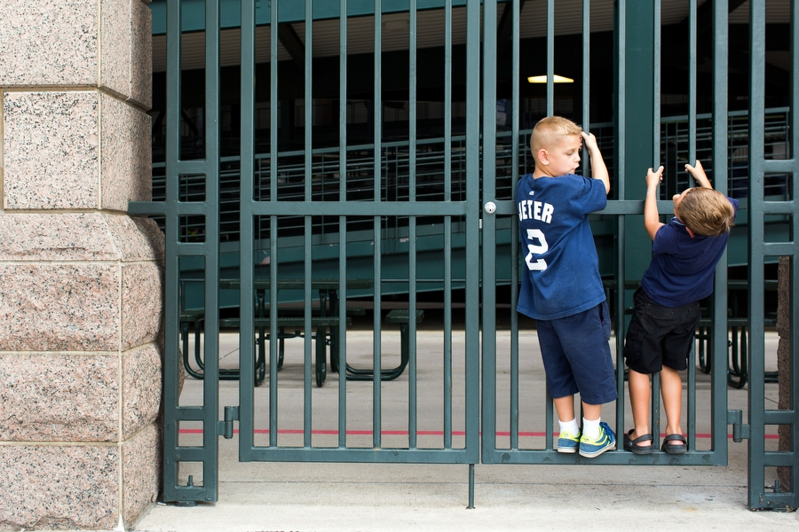 Marek Piekarski, left, and  Jeter Mariano  climb on a fence before entering the game. Marek's father said the name Marek comes from combining Yankees great Mickey Mantle's last name with Yankees great Derek Jeter's first name.