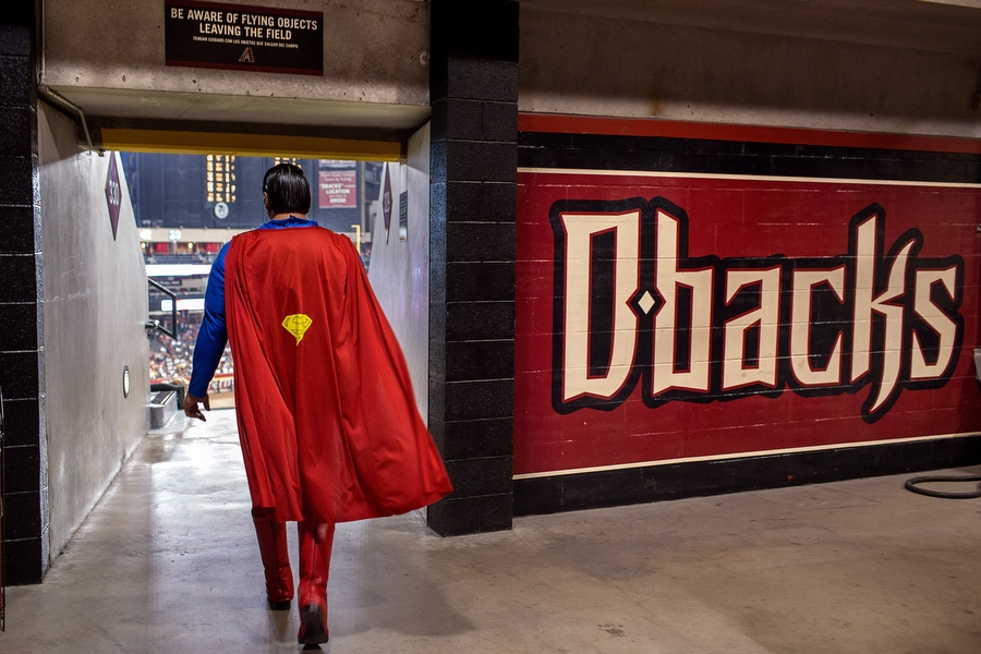 A man dressed as superman walks around Chase Field giving fans high fives and taking pictures.