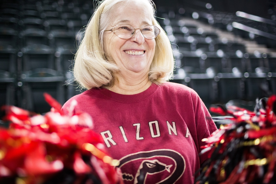 """Cindy McBride, better known as """"Flag Lady,"""" has cheered on the Diamondbacks at every home game since 2002, two games excepted. She sews and designs flags for each Diamondback regular and waves them in the upper deck whenever they bat or make a good play. She said the umpires said they were feeling left out so she made the umpires flags too."""