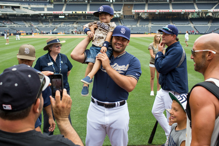Outfielder Carlos Quentin puts a fan on his shoulder before the game. On select Sundays, the Padres invite fans to take pictures with the players.