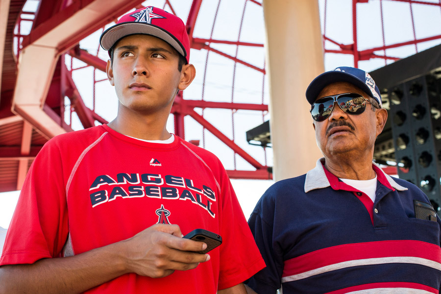 Roy, right, and his grandson Mathew wait outside the stadium before the game. Roy is an Angels fan and Mathew is a Dodgers fan. They say they don't let their competing team affiliations affect their relationship, however.