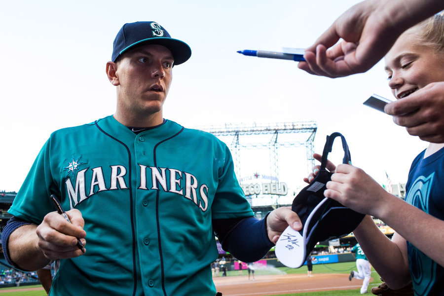 Mariners first baseman Logan Morrison signs autographs before the game.