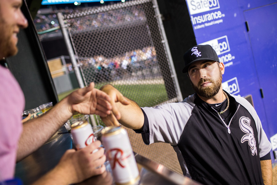 White Sox reliever Zach Putnam interacts with a fan. The distance between players in the bullpen and fans is minimal.