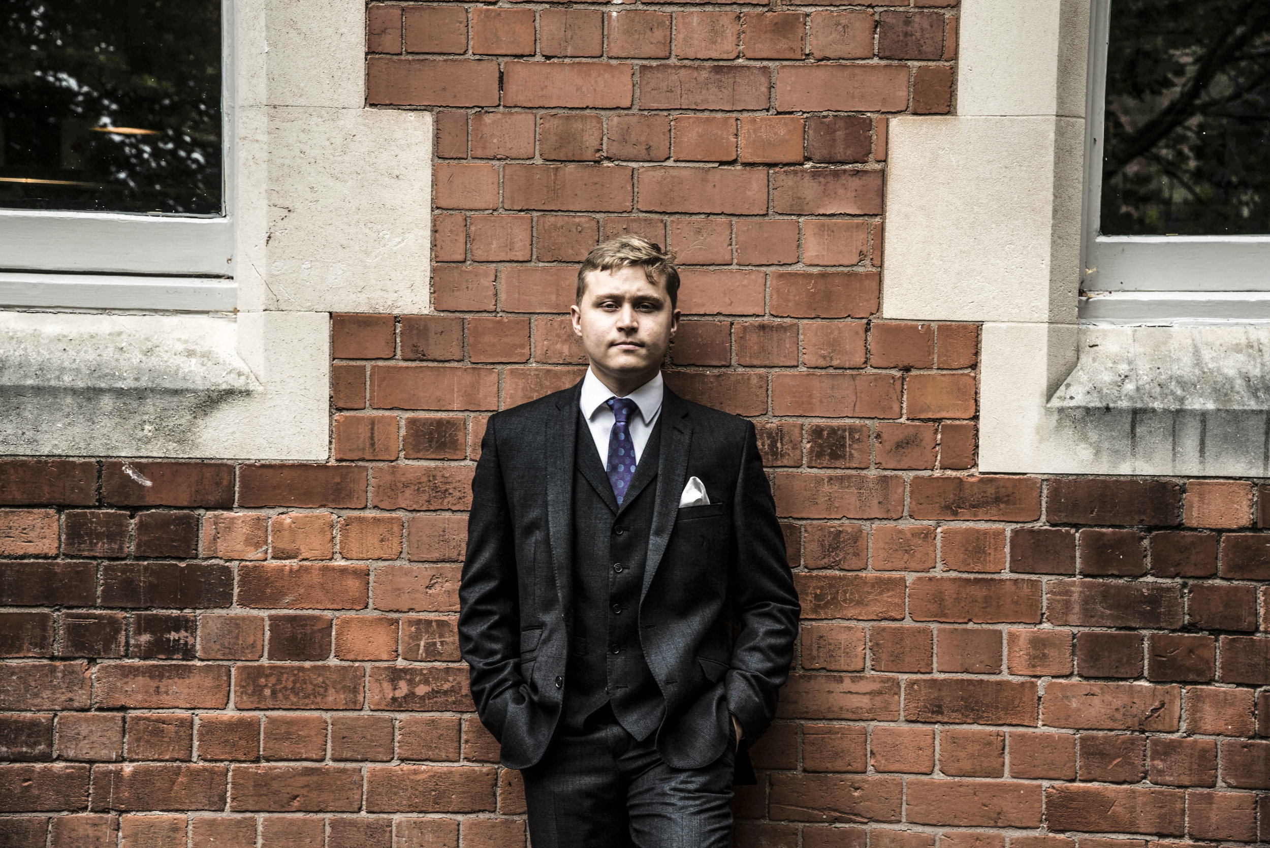 Man in dark grey suit against brick wall for web.jpg