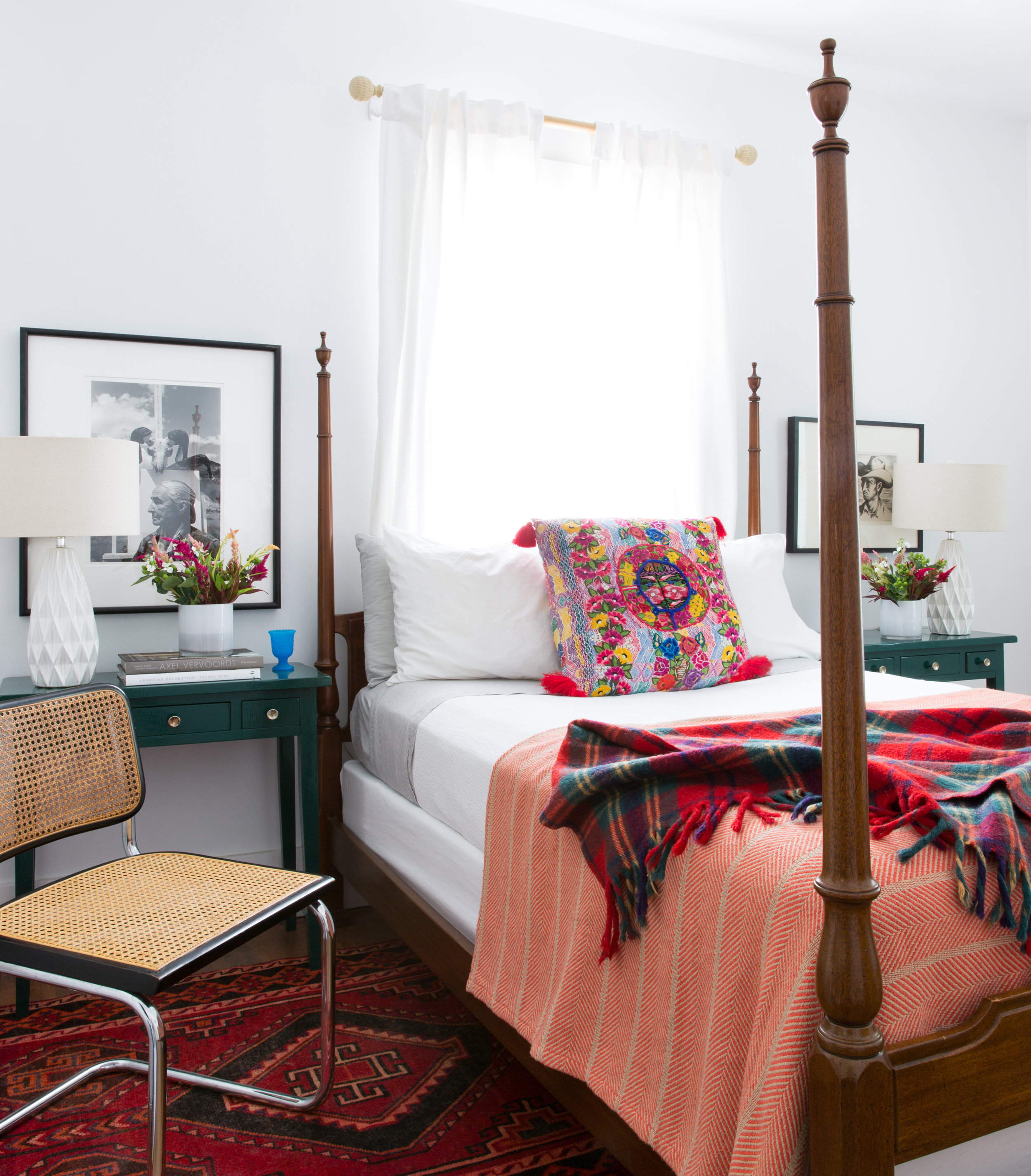 Avery Cox Design Austin Texas East Side Bungalow eclectic bedroom design with mid century modern chair, Photograph of Georgia O'Keefe, custom lacquered side tables, and an antique four poster bed.