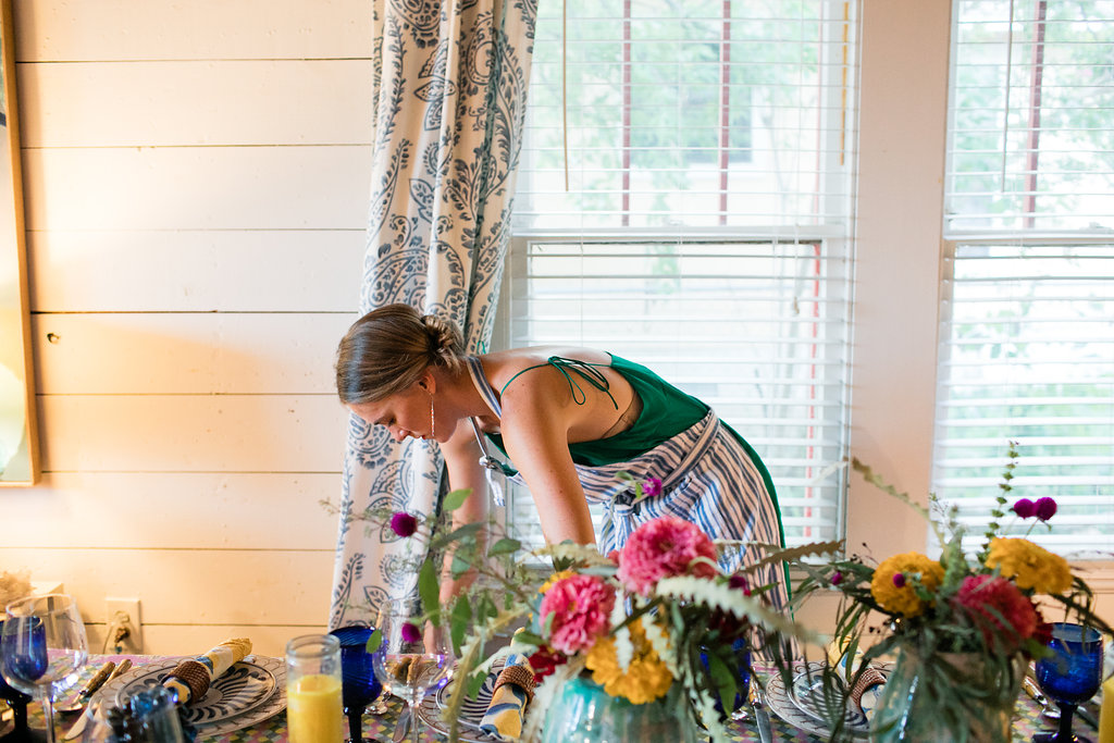 Avery Cox sets the table for her colorful Italy themed pop up dinner at her Austin Texas bungalow on a ship lap background