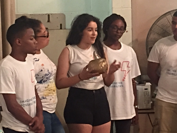 Kat Benscome, holding a golden apple from Greek mythology, encourages the JLL Volunteers to develop their creativity.