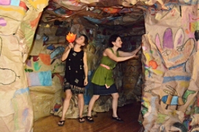 CAW Teaching Artist Lauren Genutis and Teaching Artist Assistant Karen Zasloff light up the student-produced art, based on the paleolithic cave paintings from Lascaux, France.