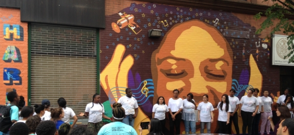 """CAW Youth Apprentices address members of the community at the unveiling of the new mural for West Harlem Group Assistance, """"Melody of Harlem."""""""