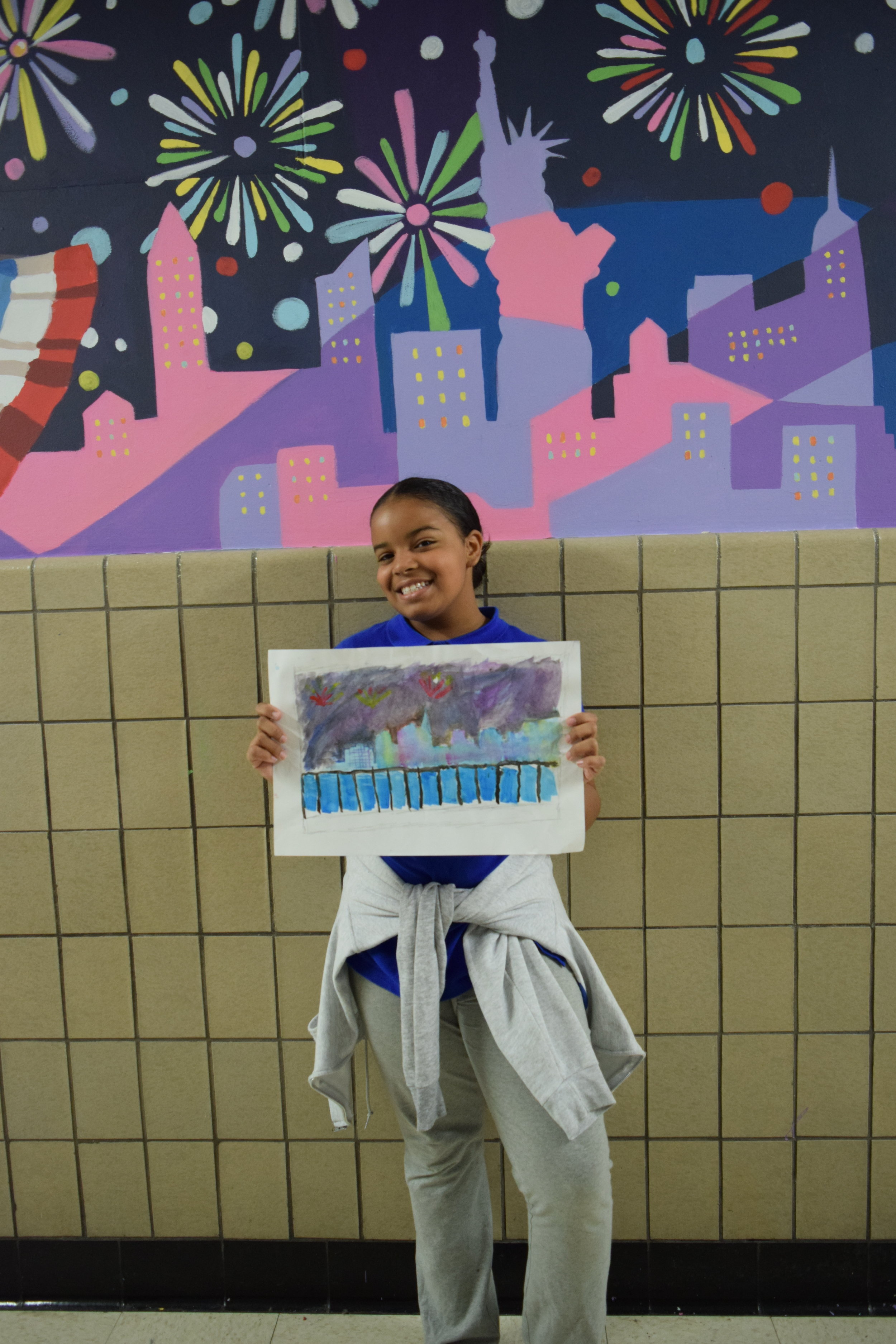 A student displays her concept sketch of the New York City skyline which was incorporated in the new mural at Hamilton Grange Middle School.