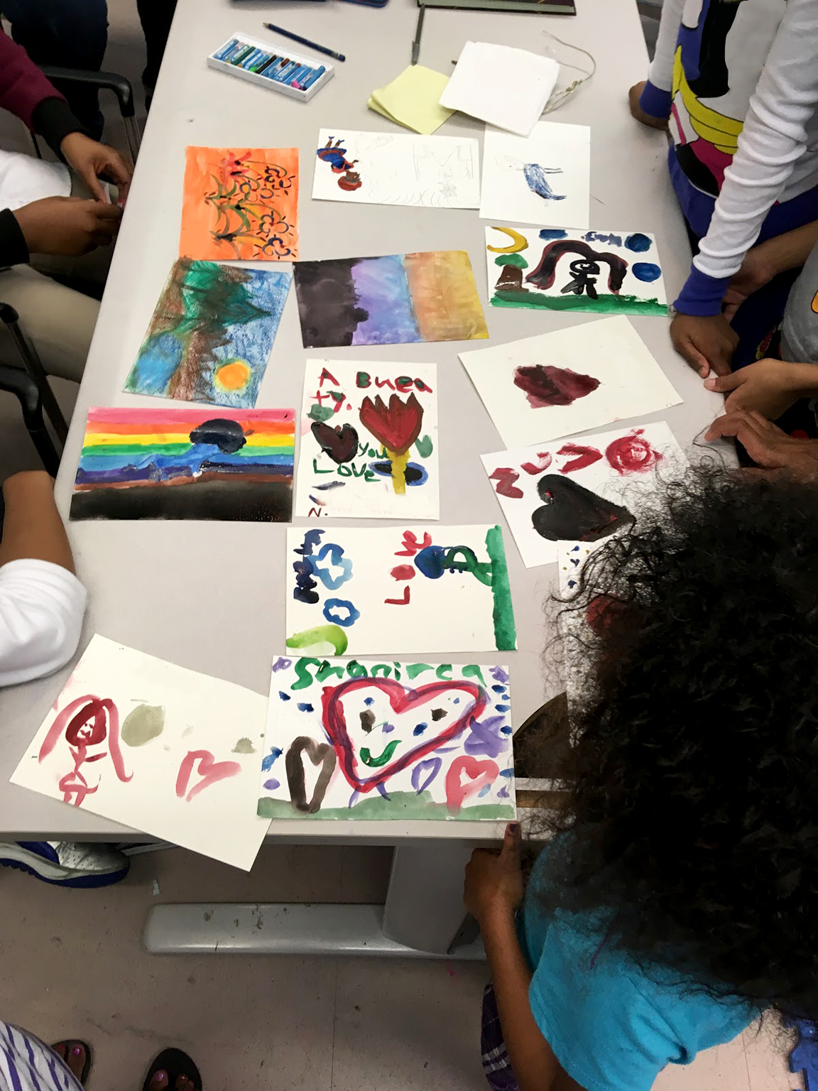 Young children painting with watercolors in the art room at the ACS Children's Center