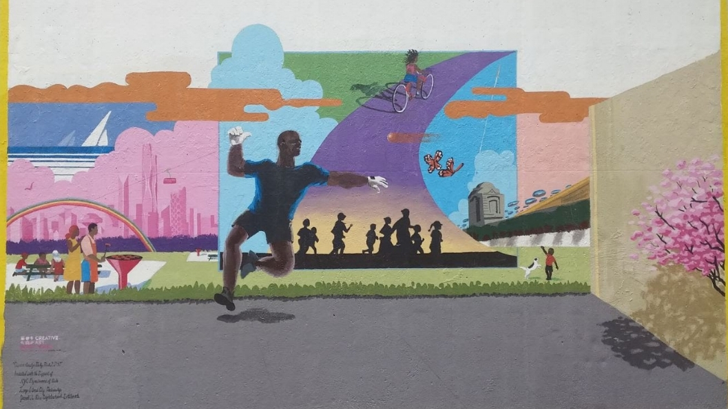 The design for the mural was based on a CAW survey of local residents and includes families enjoying a picnic, a girl riding a bicycle, a boy playing with his dog, sailboats and views of a futuristic New York City skyline and an iconic image of a man playing handball.