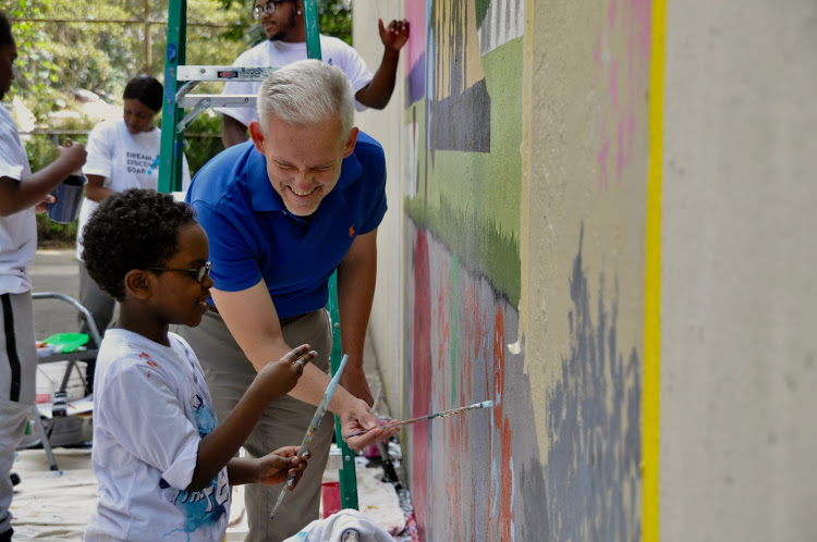 NYC Council Member Jimmy Van Bramer    paints with a Queensbridge resident. Younger children were invited to make temporary art on the lower portion of the wall throughout the day.  Photo courtesy LIC Partnership. Used by permission.