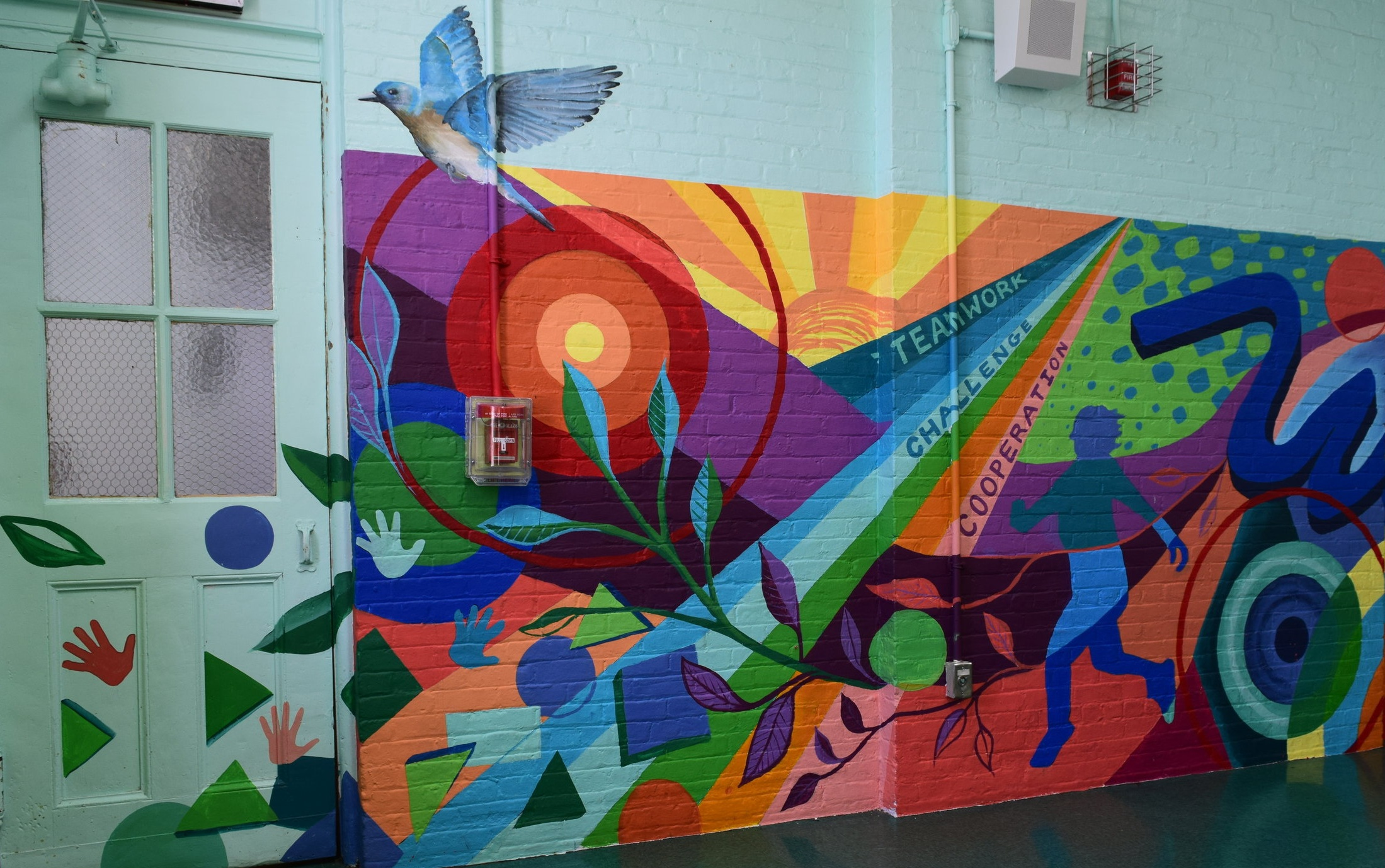 The mural at    PS 86    features hand prints, basic shapes, several bulls eyes, a sunrise, and a variety of images drawn from nature.