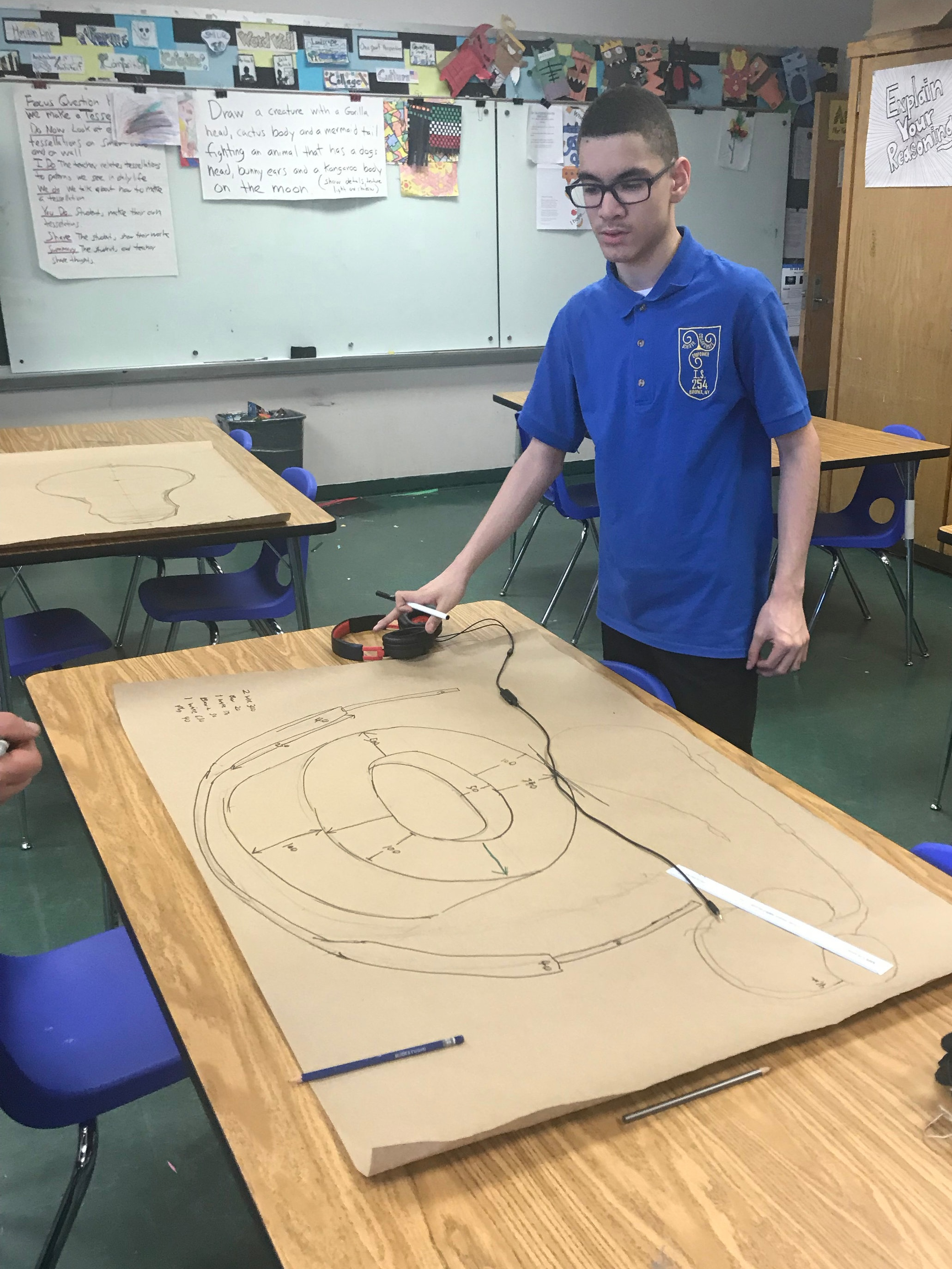 An MS 254 student with a scale drawing of his headphone many times larger than life.