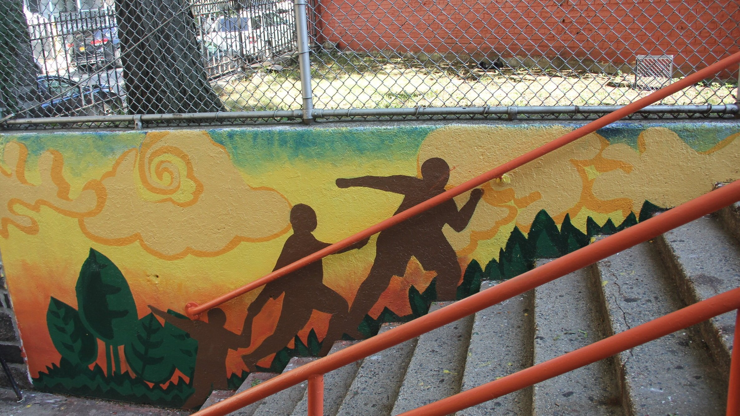 Sunrise - The murals flanking the north stairway feature abstract tropical plants and swirling clouds in shades of orange and yellow. Silhouettes of family and friends climb the stairs.