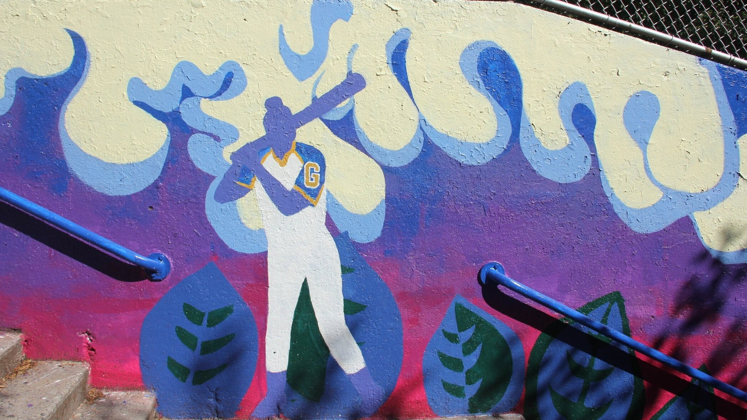 Sunset - The murals flanking the north stairway are dominated by abstract tropical plants and swirling clouds in shades of purple and blue, and features silhouettes of students engaged in study, public speaking and sports.