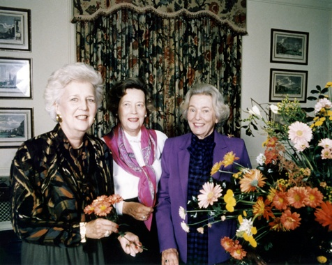 "Virginia Bissell (later Spencer), left, Lula Rose Blackwell and Beverley Dunn prepare for the Williamsburg Seminar.    In 1985 Oxmoor House, Inc., Book Division of Southern Progress Corporation, published Elegance In Flowers, based on the Birmingham style and featuring the talents of many members of LGC and RMGC. John Floyd, editor of Southern Living Classics, wrote the forward to the book and said that the arrangements were ""true to the nature of the materials as living, growing things."" We are proud that our members were recognized for their floral accomplishments and in the next several years many were invited to participate in the Williamsburg Symposium, the Philadelphia Flower Show and the Chelsea Flower Show.    The Little Garden Club held a series of flower demonstrations and lectures at the BBG as a means of fundraising for community projects. In the early 80s Norman Johnson, a noted landscape designer, presented a symposium on home landscapes. A few years later, he spoke on ""Bulbs in the Landscape"" in conjunction with a LGC bulb sale. In 1988 we hosted a lecture by interior designer Alexandra Stoddard. Beginning in 1989, along with the Birmingham Botanical Society, now called the Friends of the Birmingham Botanical Gardens, LGC offered a series of flower arranging classes taught and assisted by our members. These workshops included four sessions and were held October through April for four years. LGC sponsored English flower arranger Sheila Macqueen whom many members knew from attending her workshops in England. Later, we invited Mrs. Macqueen's colleague Fred Wilkinson of the Constance Spry School in England for a lecture and demonstration.    As an entry in the 1985 GCA Horticulture Committee's competition, LGC designed and financed a holly border at the Birmingham Botanical Gardens. When the newly designed Gatehouse Gift Shop opened at the BBG, one of our members assumed management, expanded the inventory, and took the shop to new heights. Several members of The Little Garden Club volunteered hours to help staff the shop. Many gave tours of the Gardens putting in place a successful docent program. One of our members served as education director for the BBG and several LGC members have served on the board of the Botanical Society, with three having served as President.    In the fall of 1985, LGC hosted the Zone VIII meeting held at the Sheraton Perimeter Hotel. The theme of the meeting was ""Back to Basics in Birmingham"" and included a Pot en Fleur workshop for delegates. Private dinners, a flower show, and educational horticulture and conservation meetings rounded out the event.    In 1986 The Little and Red Mountain Garden Clubs co-sponsored a flower show at the Birmingham Museum of Art, where members interpreted or complemented works of art in the collection. The success and public enthusiasm for this show inspired members of the Museum Art Education Council (MAEC) to sponsor a similar flower show the following year as a fundraiser for education programs. Calling on members of the two garden clubs for advice, MAEC volunteers presented their first Art in Bloom in 1987 and their ninth and most recent event in 2006. Members of LGC continued to participate as planners or by entering their interpretive arrangements in the exhibitions."