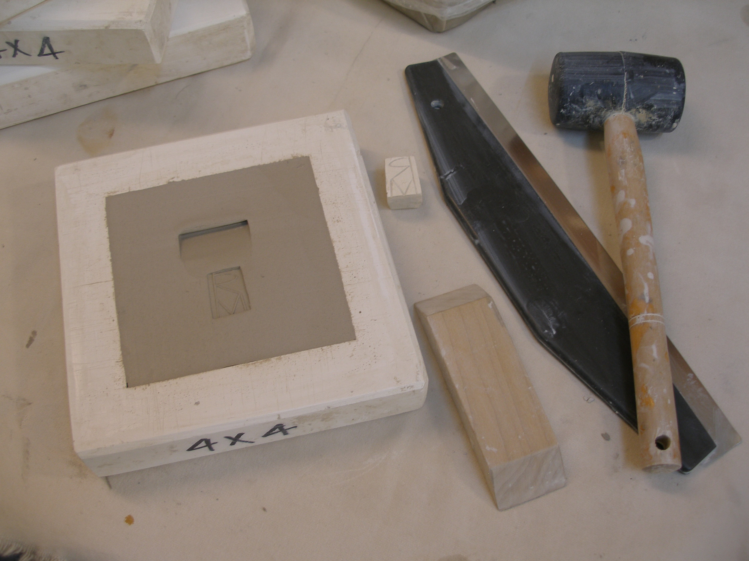The excess clay is sliced off with a wire tool, and the back of the tile is scraped and smoothed flat. A beveled piece of wood is pressed in to create an indentation for hanging. The tile is also stamped with the maker's mark.  The tile will dry for several hours. As the plaster draws moisture from the clay, the tile begins to shrink away from the mold. The mold can then be inverted onto a board, the tile will drop out, and the mold removed.