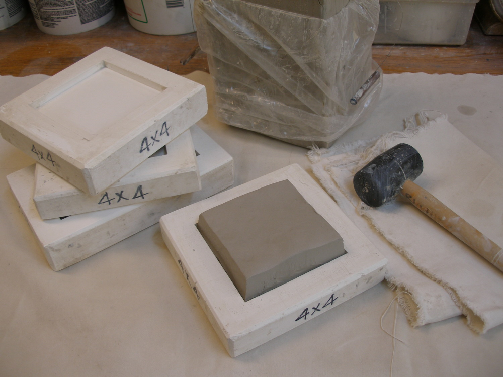 A plug of white stoneware clay is cut to conform to the size and shape of the plaster mold. This plug is much thicker than the final tile will be. The extra clay protects the edges of the plaster as the clay is pounded into the mold with a rubber mallet.