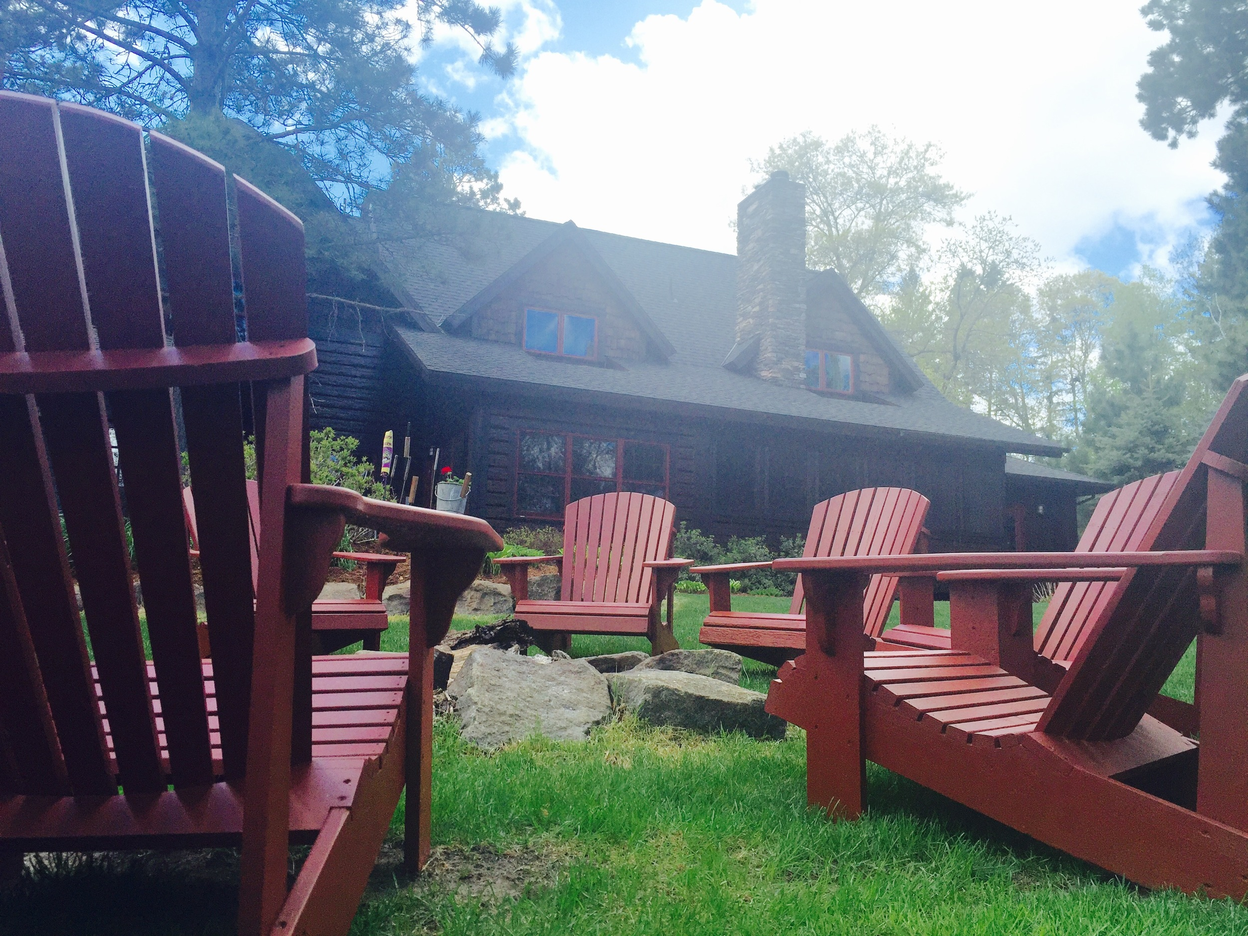 Freshly painted adirondack chairs tie in the right pop of color to this lake home.
