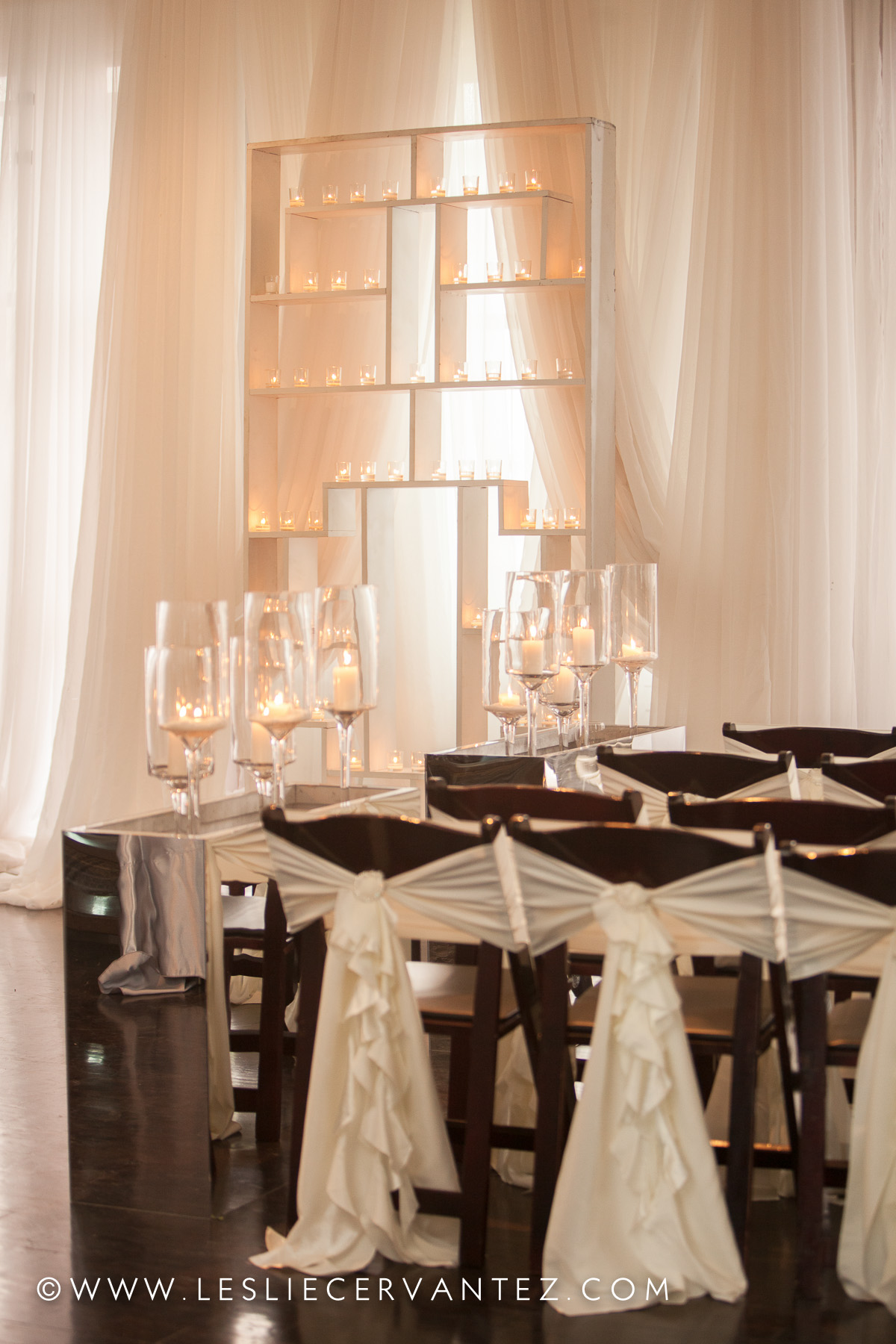 Candle wall, draping and aisle decor provided by Flora & Eventi; chair ties provided by Over the Top Linens