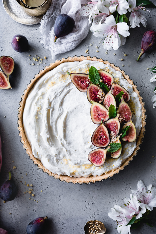 No-Bake Fig Tart - Crust:Graham cracker crust or Shortbread crustFilling:Heavy cream, chilled - 1 cupCream cheese, at room temperature - 8 oz.Raw sugar - 3 TBSPPowdered sugar - 5 TBSPHalved figs, and crushed pistachios for toppingHoney to drizzle the figs (optional)