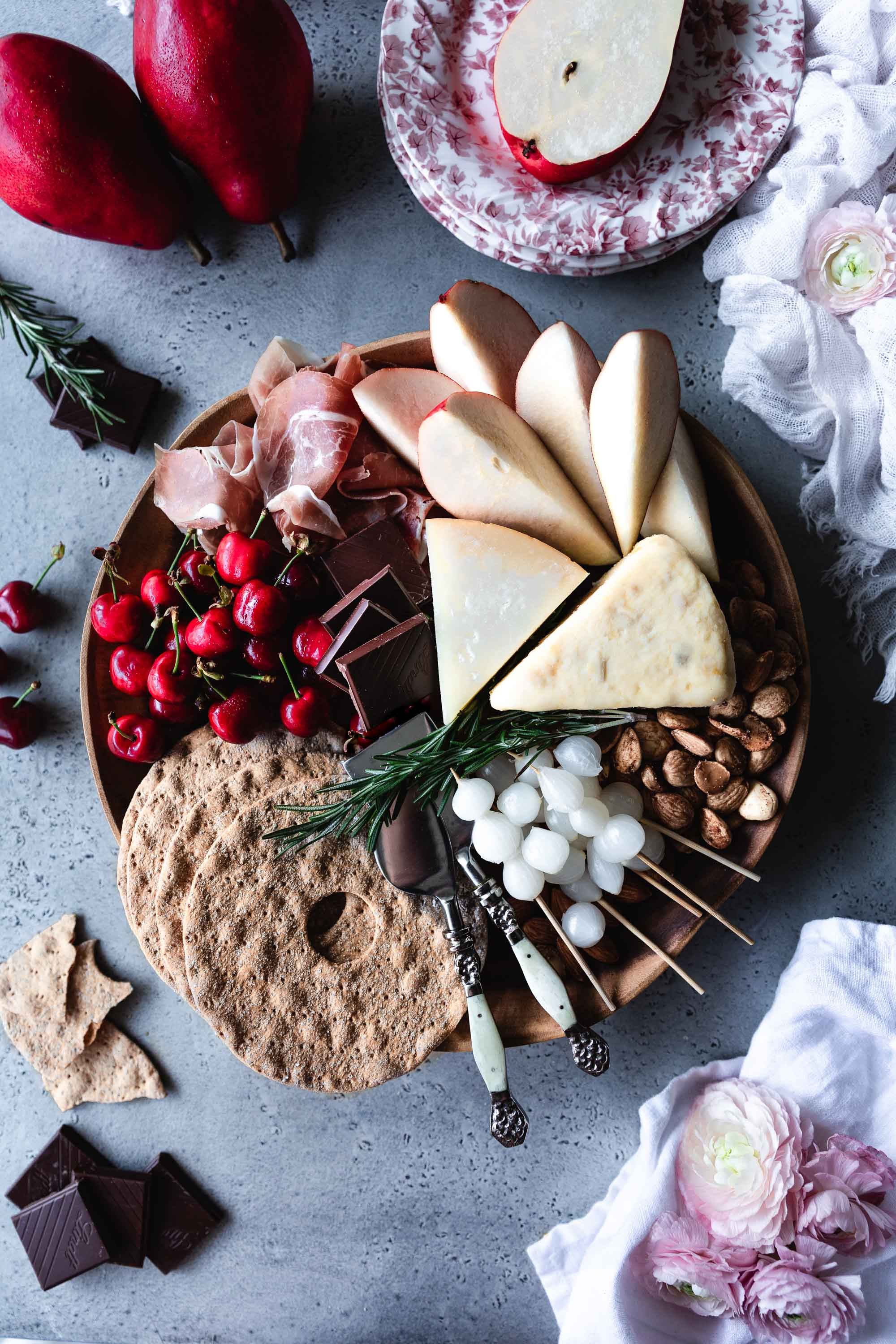 (A cheese tray with Manchego, stilton, prosciutto, cherries, red pears and spicy dark chocolate with chilli fakes)