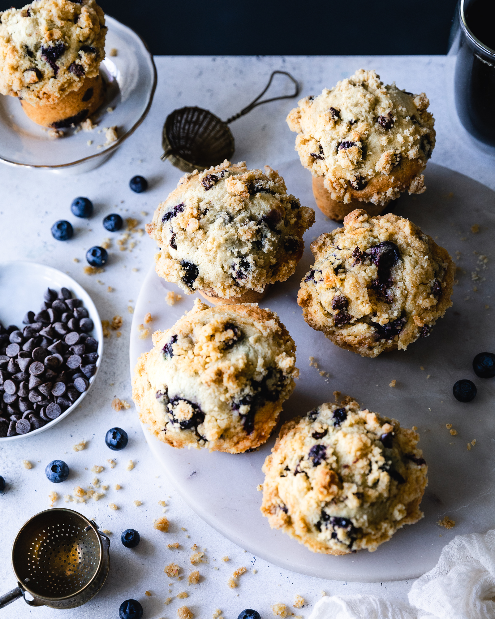 Blueberries & Chocolate Chip Muffins - CrumbRaw sugar – 4 TBSPBrown sugar – 4 TBSPUnbleached all purpose flour – ⅔ cupButter, semi softened – 5 TBSPPinch of fine sea saltMuffin batterSemi-sweet chocolate chips – 1 ½ cupUnbleached all purpose flour – 2 ½ cups + 1 ½ TBSPBlueberries, preferably frozen (see notes) – 1 ½ cupAlmond flour – ½ cupBaking powder – 4 TspFine sea salt – 1 TspRaw sugar – 1 cupOrganic free range eggs – 2Ricotta cheese – ½ cupVegetable oil – ½ cupCoconut milk – 1 cupPure vanilla extract - 1 Tsp