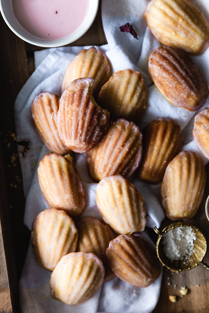 Frangipane Madeleines with Hibiscus Glaze - FrangipaneUnsalted butter – 7 TBSPRaw organic sugar – ¼ cupAlmond flour, or finely grinded almonds – ¾ cupEggs, room temperature – 2Madeleines' BatterOrganic unsalted butter – ½ cup (1 stick) + 2 TBSP for the panOrganic free range eggs, at room temperature – 2Raw sugar – ½ cupPure vanilla extract – 1 TspUnbleached all purpose flour, sifted (see notes)– 1 cupBaking powder (optional) – ⅛ TspFine sea salt - ⅛ TspHibiscus GlazeHibiscus flower – ¼ cupWater – 1 cupConfectioner's sugar, sifted – 2 cup
