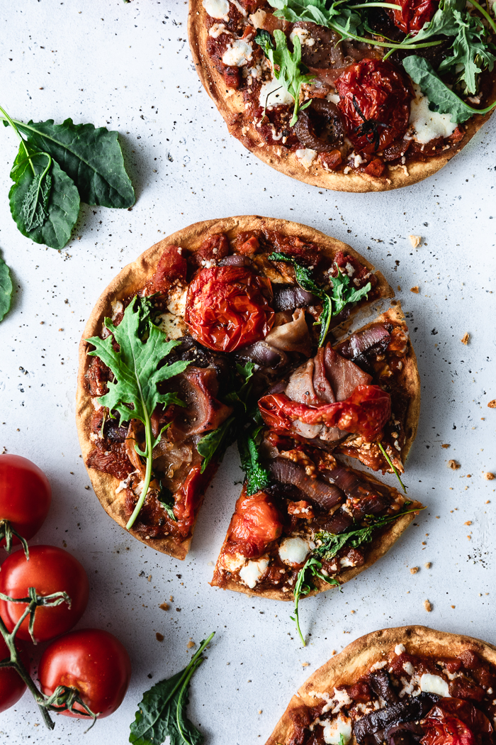 """Roasted Tomatoes and Balsamic Vinegar Onions Naan Bread Pizzas - Red onion, sliced in ¼"""" thick slices – 1 largeFine sea salt – about 1 Tsp, dividedFreshly ground black pepper – ½ Tsp, dividedBalsamic vinegar – 1 to 2 TBSP (see notes)Campari, Roma or plum tomatoes – 12 Campari or 6 Roma or plum cut in halfPinch of raw sugarNaan bread – 4Olive oil – 2 TBSP + 3 TBSPBertolli Rustic Three Cheese tomato sauce – ½ cupFresh mozzarella – 8 slicesProscuitto slices – 8Basil, kale or arugula leaves if desired"""