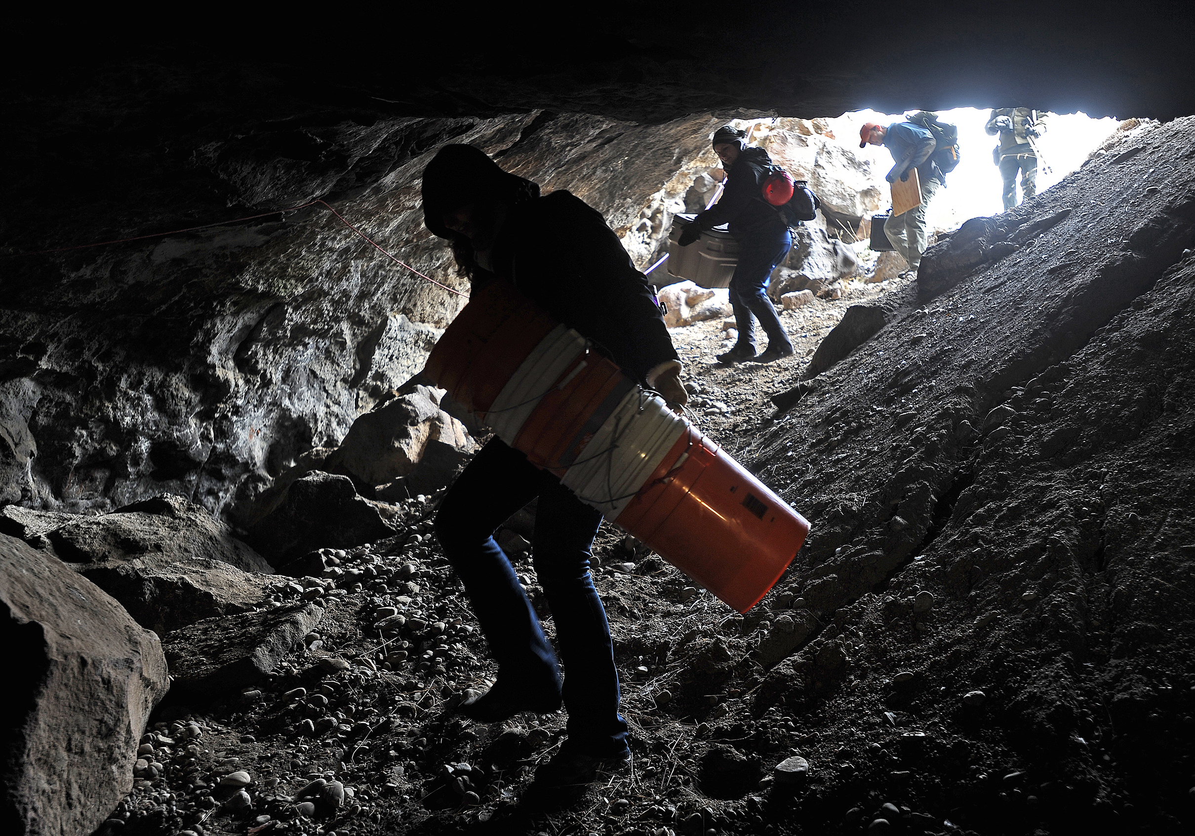 Undergraduate and graduate students carry in an array of supplies they will use to search and excavate designated parts of the cave Feb. 27 in Dubois.