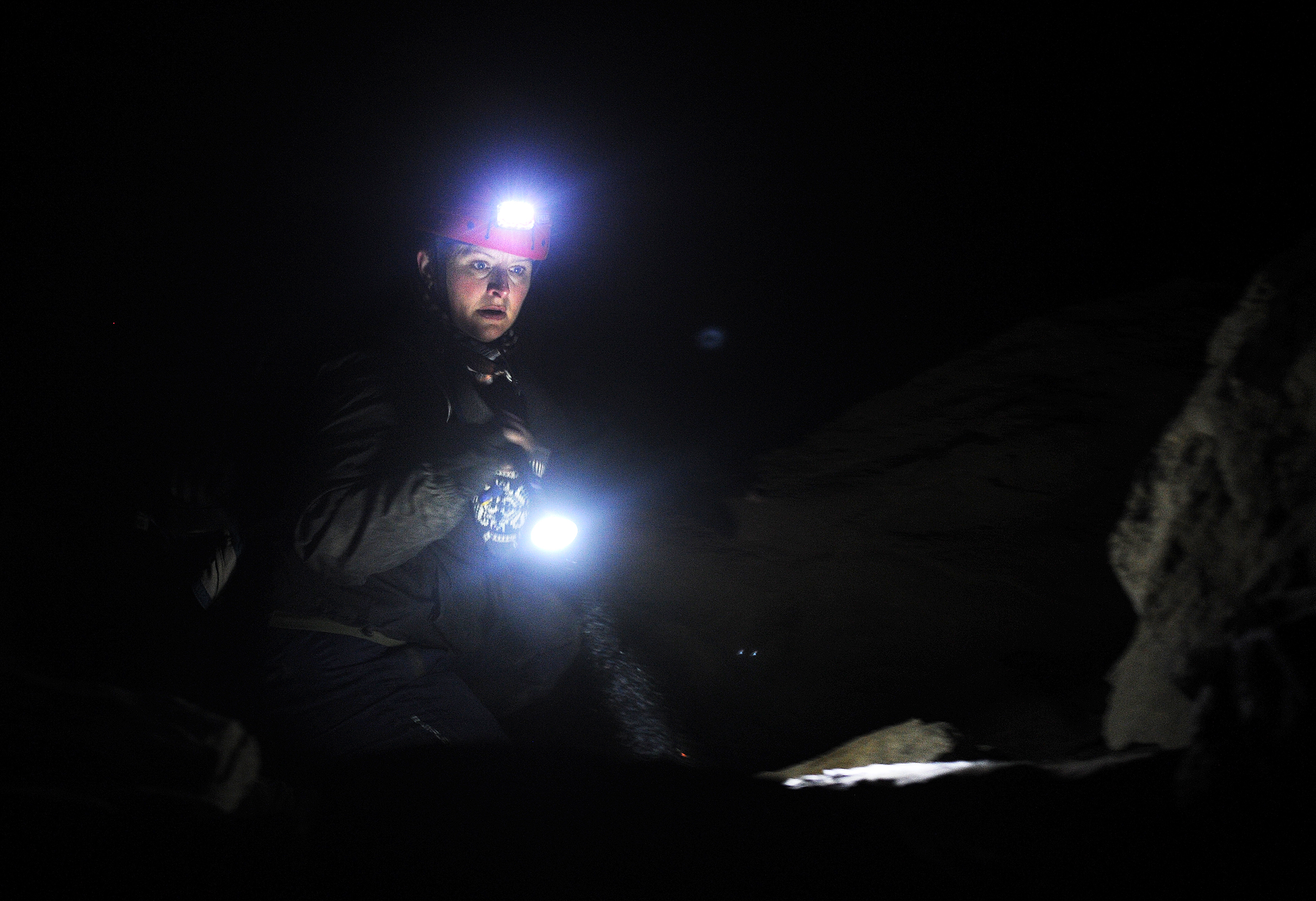 Daria Van Dolsen, a graduate student at Idaho State University studying anthropology, searches rock formations in the back of the cave for any unseen crevices that the head could have been hidden in.