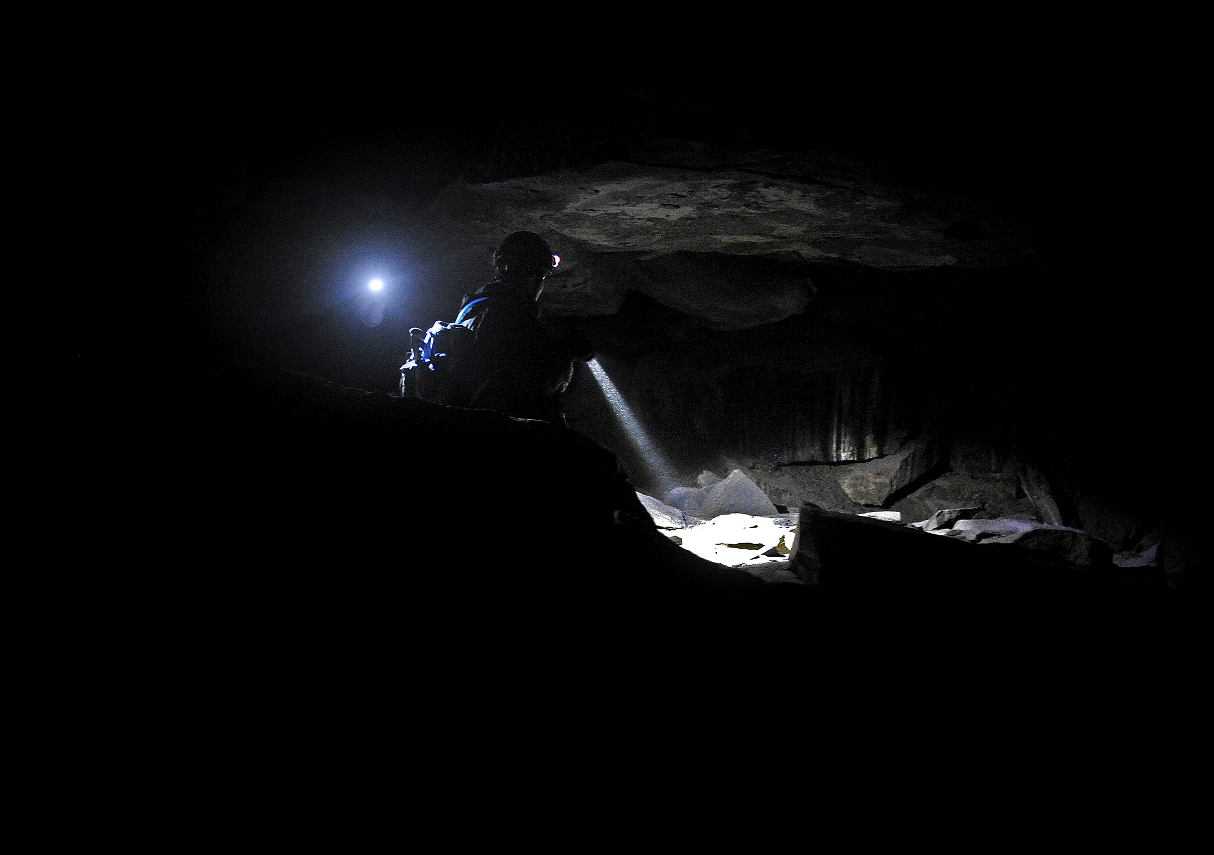 Eli Taysom, a first year graduate student studying biological anthropology, and Daria Van Dolsen, a graduate student studying anthropology, search the back of the cave for any locations the head could have been hidden. Because of the rough rock formations and hidden crevices, Clark County Sheriff's Department was unable to hang lights this far back in the cave, leaving the search to Taysom and Dolsen's helmet lights.