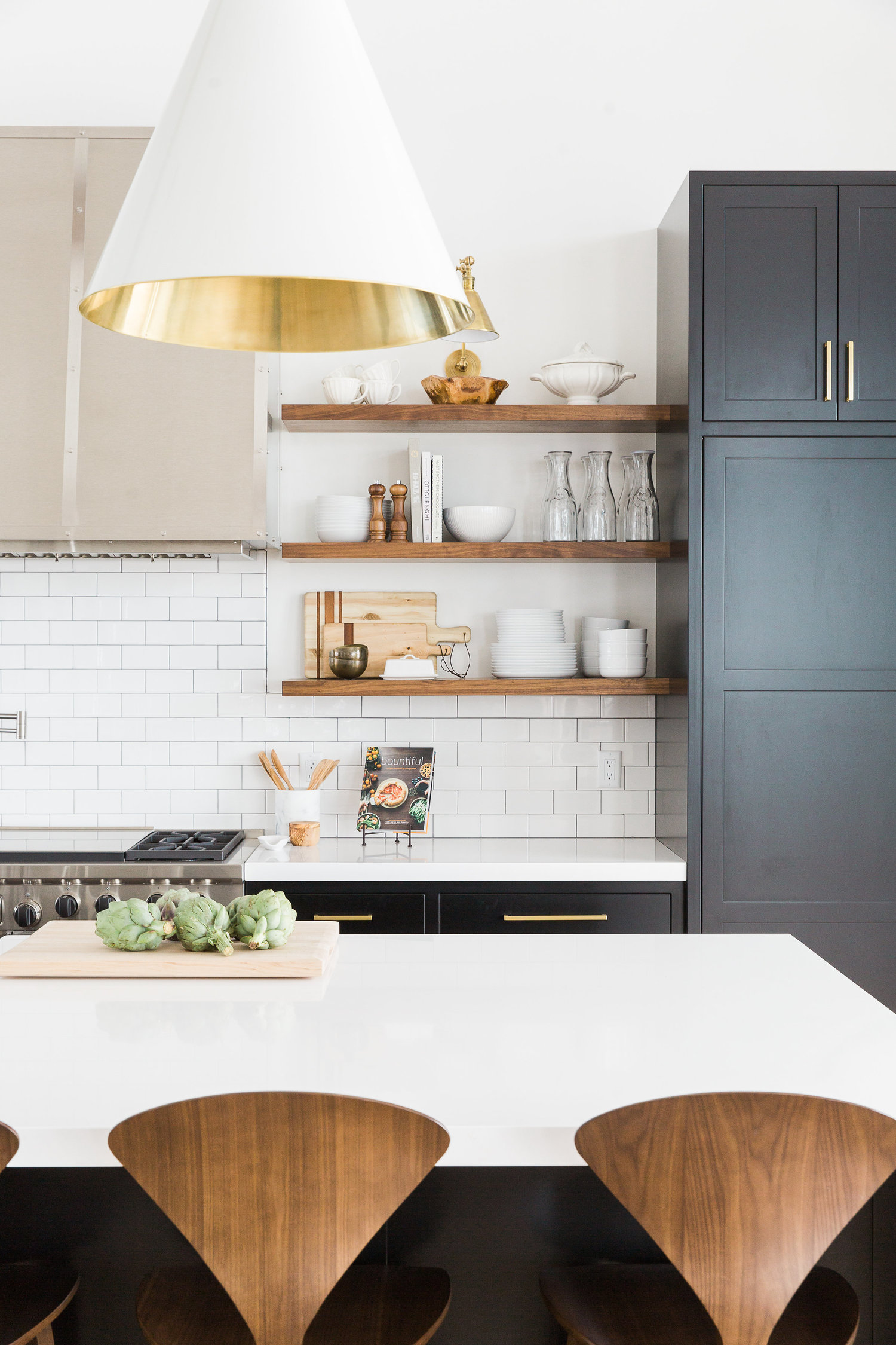 White and gold light fixture of kitchen island