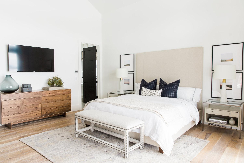 Wooden dresser next to king bed in bedroom