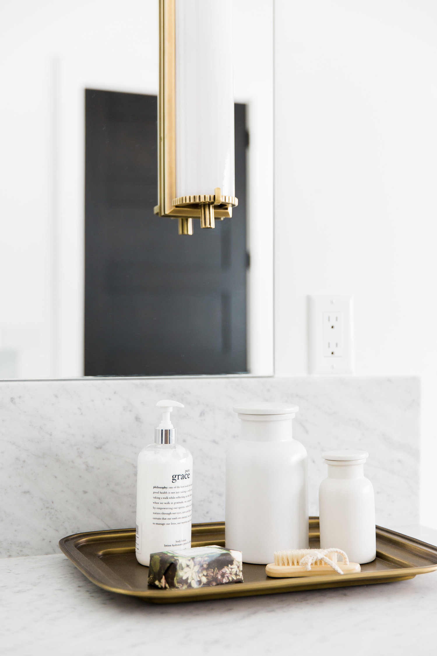White lotion bottles on gold tray in bathroom