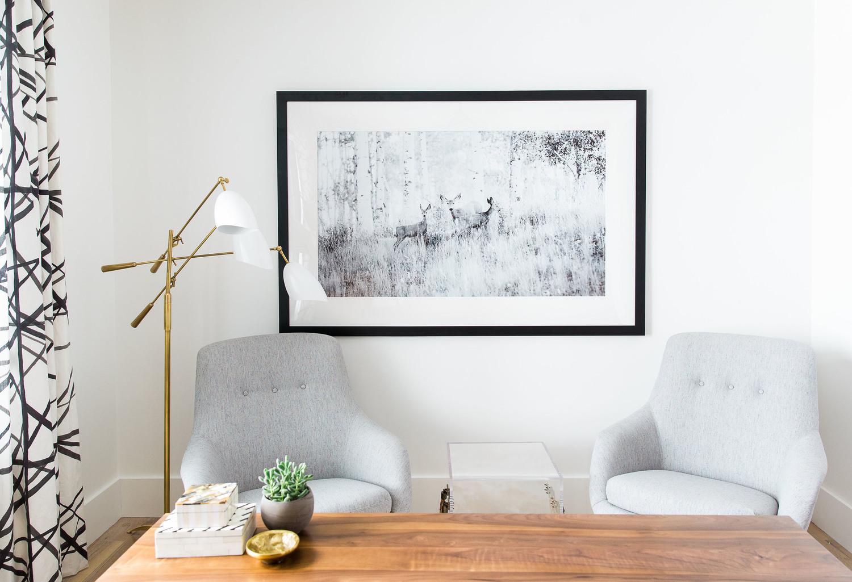 Grey wall art behind two grey sofa chairs