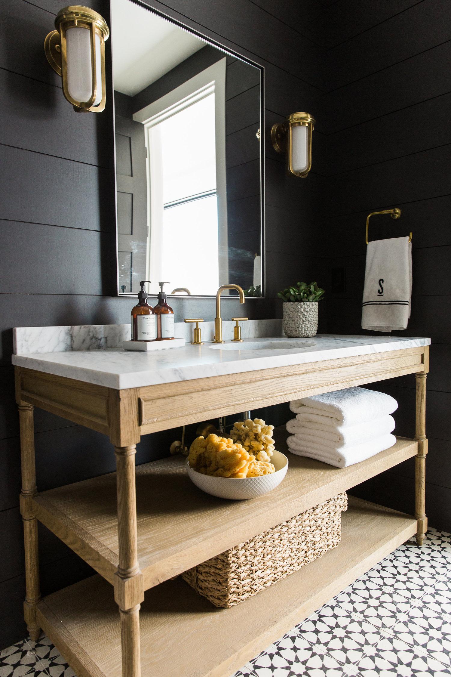 Wooden vanity beneath large mirror
