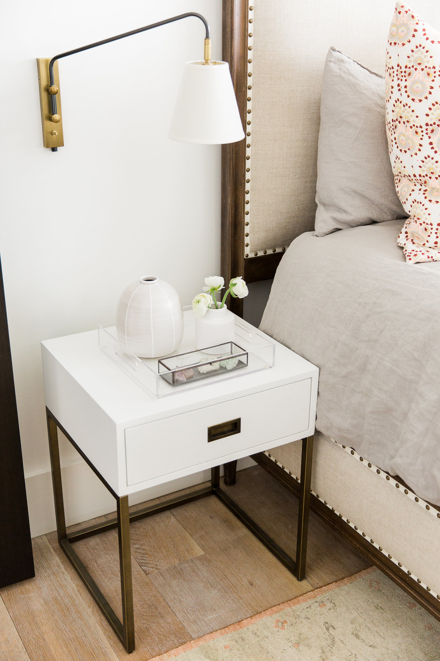 Minimalist white nightstand next to bed