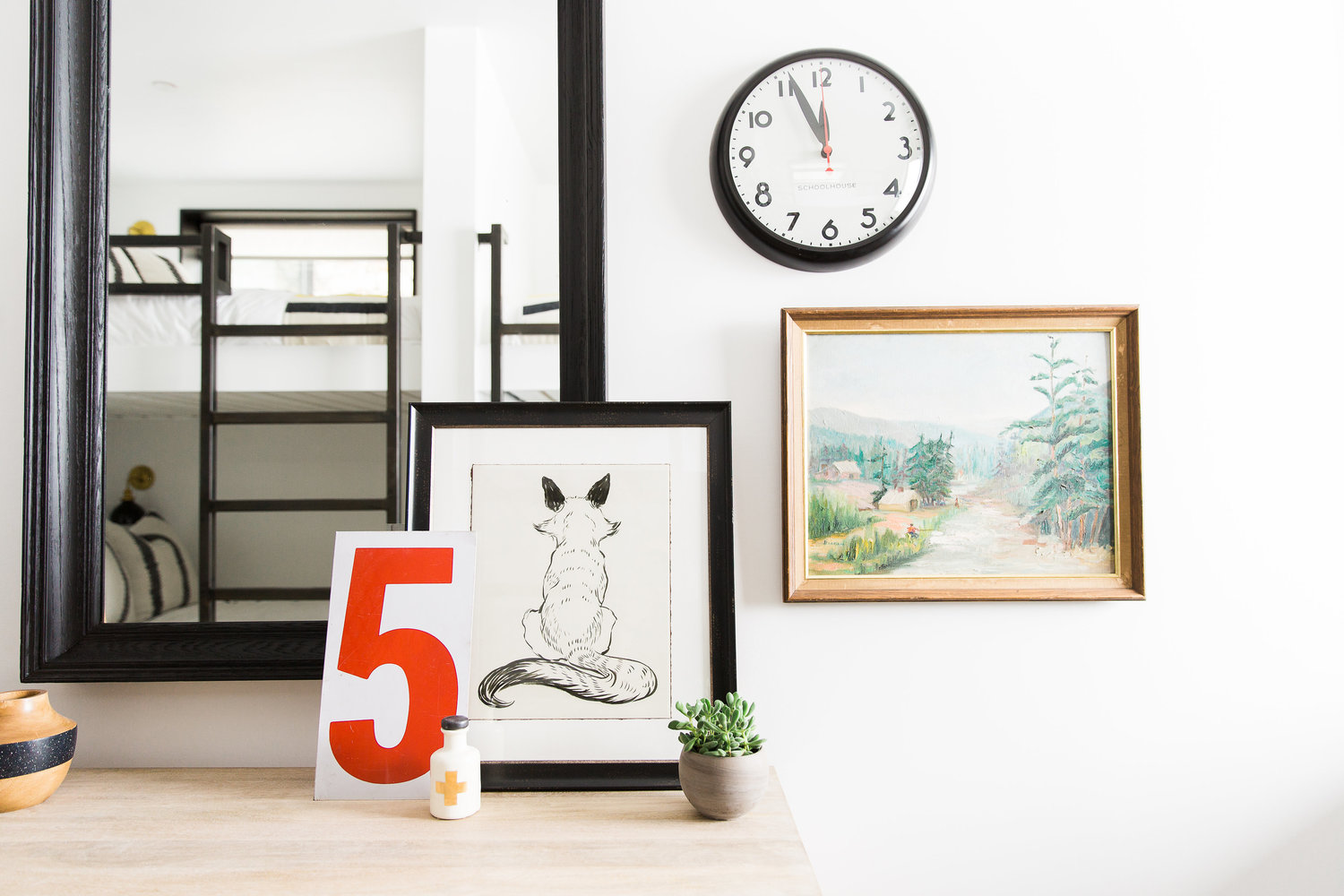 Mirror beside clock and wall art in house